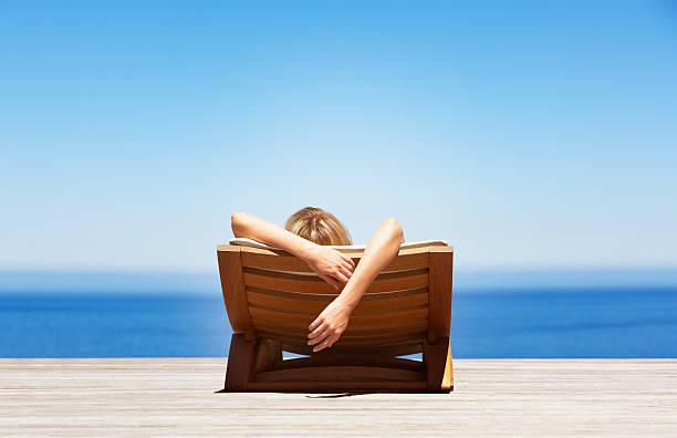 vista traseira da mulher relaxar na cadeira dobrável ao ar livre - escapismo - fotografias e filmes do acervo