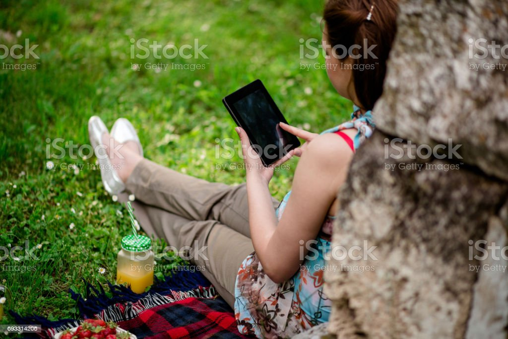 Rear View Of Brown Haired Woman Using Tablet And Enjoying The Day