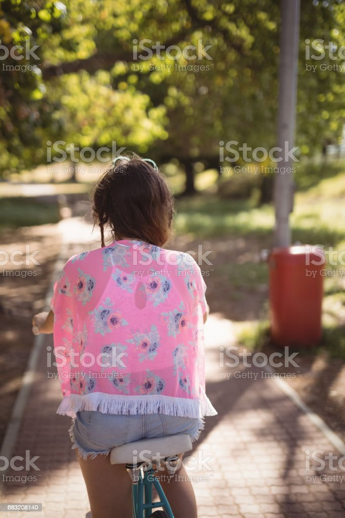 Rear view of woman riding bicycle on footpath foto de stock royalty-free