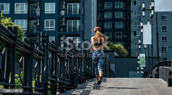istock Rear view of woman running on city road with modern buildings in the background 1299124919