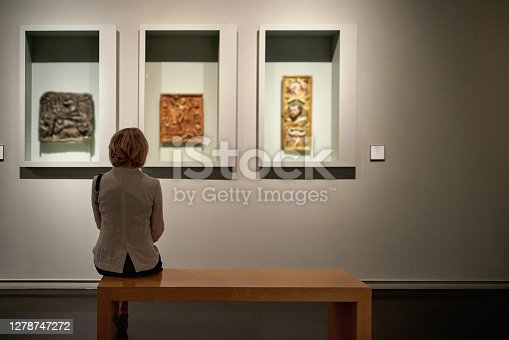 rear view of woman sitting in an art gallery in front of colorful paintings