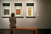 istock rear view of woman sitting in an art gallery in front of colorful paintings 1278747272