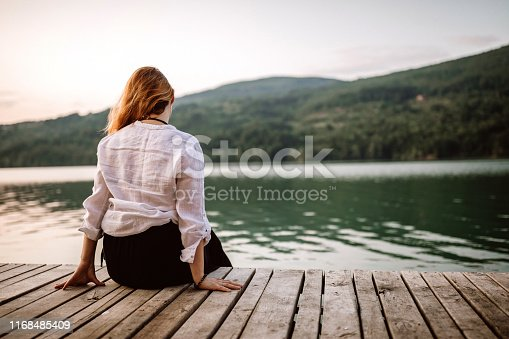 Rear view of woman sitting on pier and enjoying view on lake, on summer day