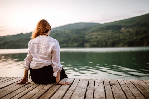Rear view of woman sitting on pier and enjoying view stock photo