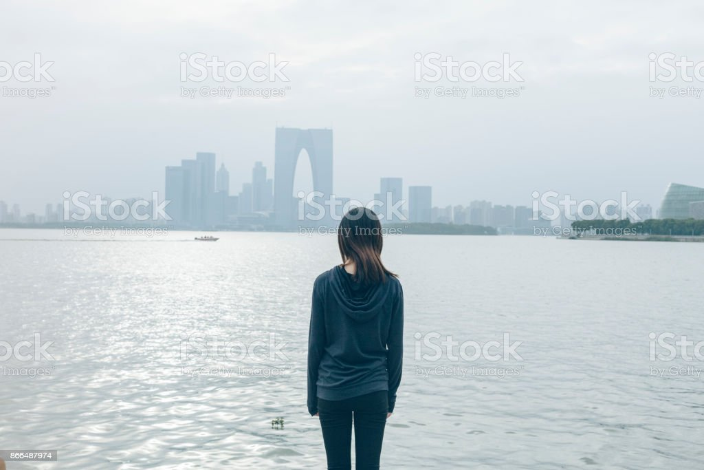 rear view of woman standing by lake viewing beautiful secnery,suhzou...