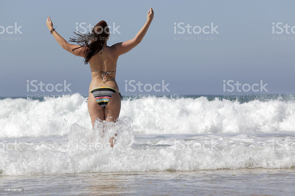 Rear view of woman standing in waves raising arms (XXXL) royalty-free stock photo