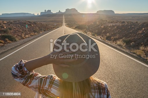 Rear view of woman standing on long highway road leading to Monument Valley in USA. People travel America concept