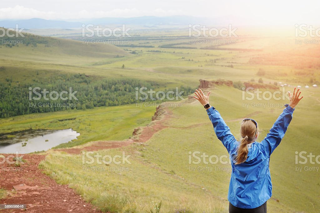 Rear View Of Woman Standing On Mountain With Arms Outstretched. stock photo