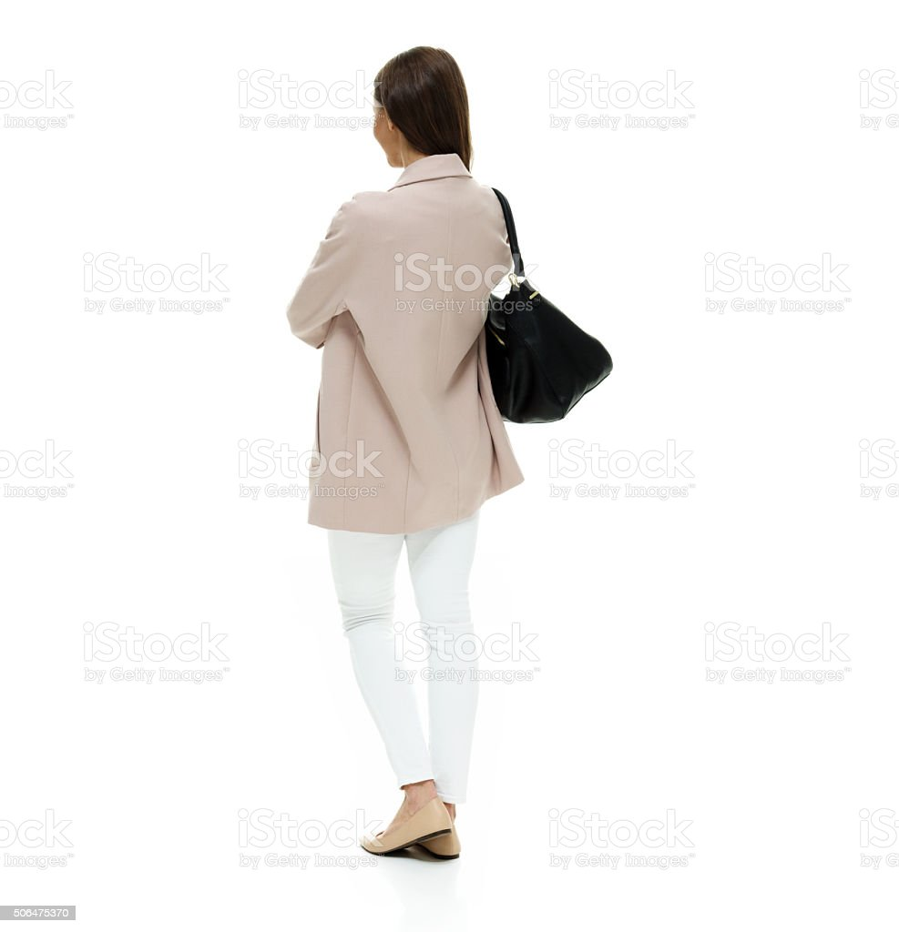 Rear view of woman standing with arms crossed stock photo