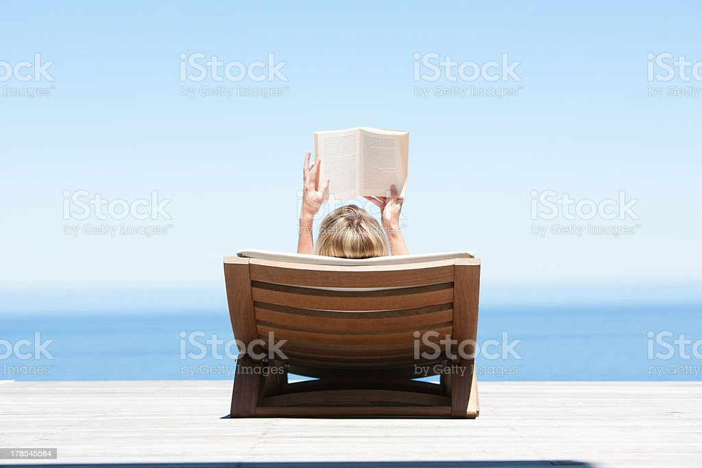 Fabulous Rear View Of Woman Sunbathing On Folding Chair With Reading Gmtry Best Dining Table And Chair Ideas Images Gmtryco