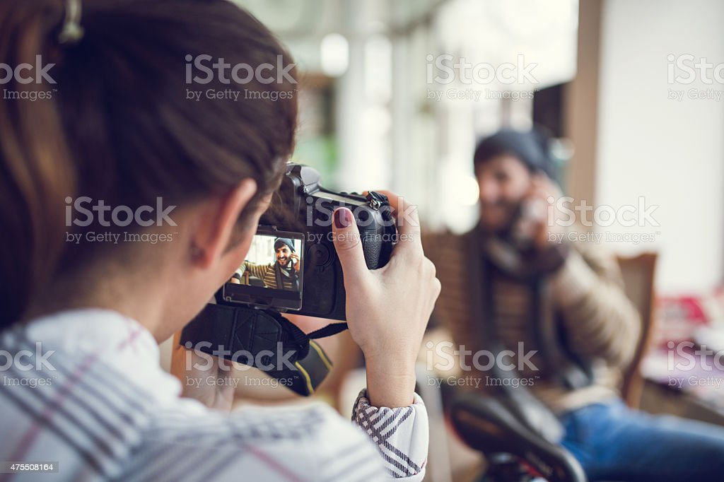 Rear view of woman taking a photo with digital camera. stock photo