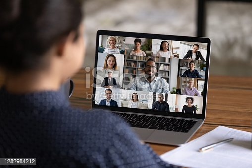 Over shoulder view of female worker have webcam digital virtual conference with diverse multiethnic colleagues. Woman speak talk on video call with multiracial businesspeople. Online meeting concept.