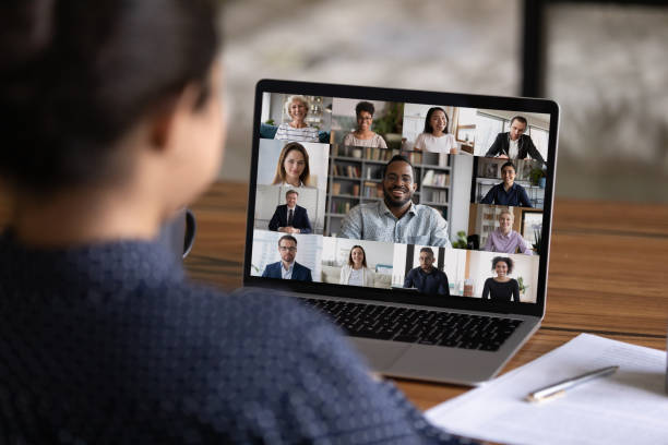 Rear view of woman talk on video call with colleagues stock photo