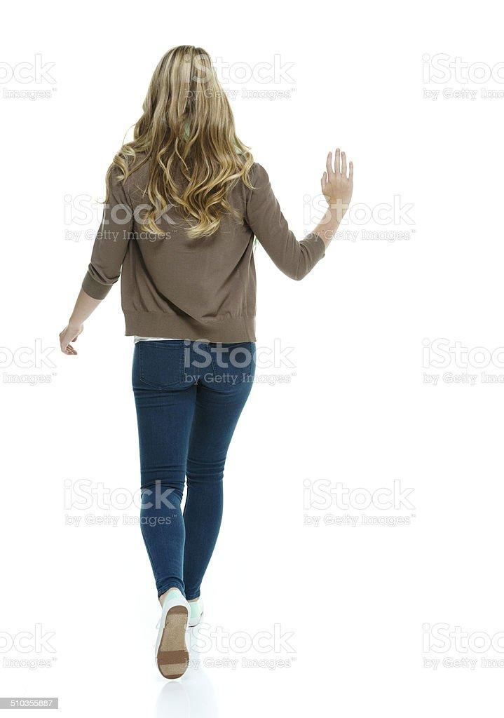 Rear view of woman walking and waving stock photo