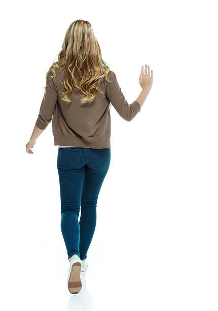 vue arrière de femme marchant et agiter les mains - fille dos photos et images de collection