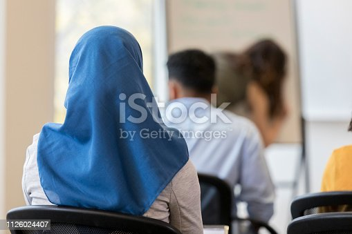 In this closeup rear view, an unrecognizable woman wearing a hijab sits in a chair in a classroom.  Other classmates sit in front of her.