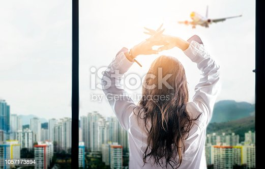 Rear view of woman with long hair standing at window side and looking at city view while the airplane fly over