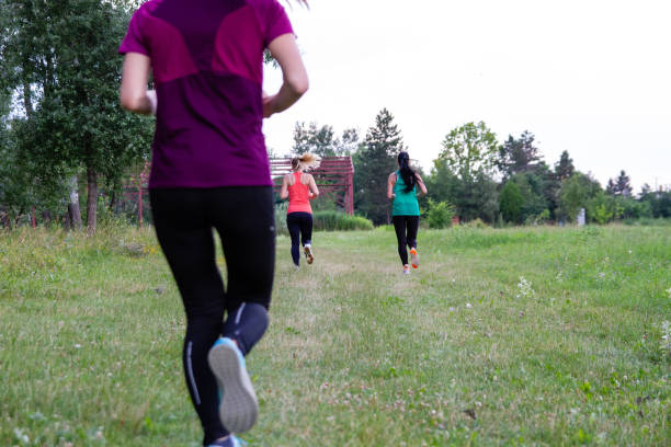 Rear view of women running stock photo