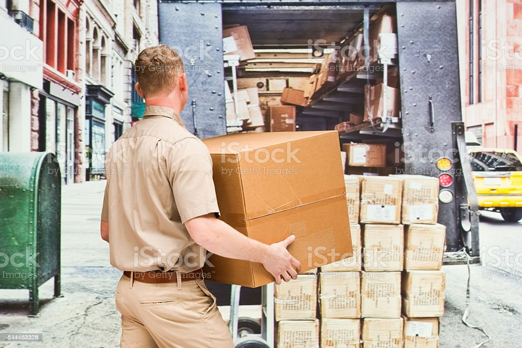 Rear view of worker holding box outdoors stock photo