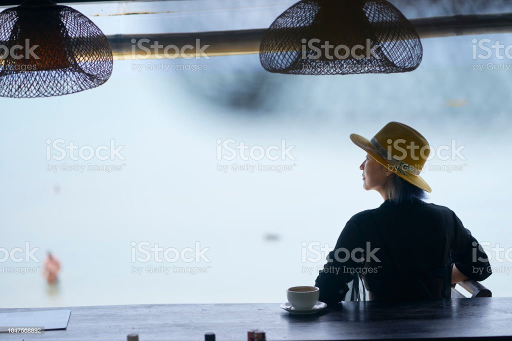 rear view of young Asian beauty sitting, relaxing at beach bar in vacation stock photo