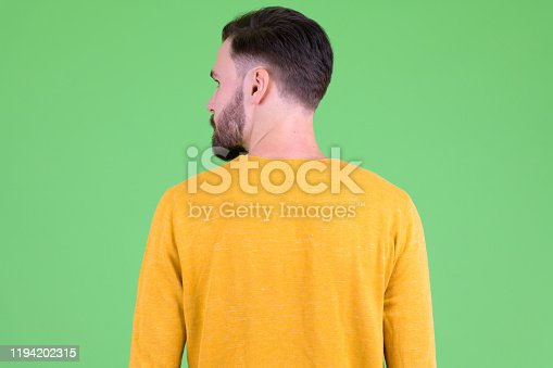 Studio shot of young handsome bearded man against chroma key with green background