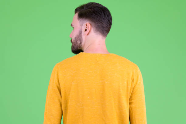 Rear view of young bearded man looking over shoulder stock photo