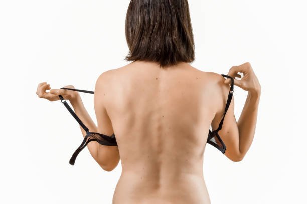 Rear view of young beautiful brunette woman taking off her bra stock photo