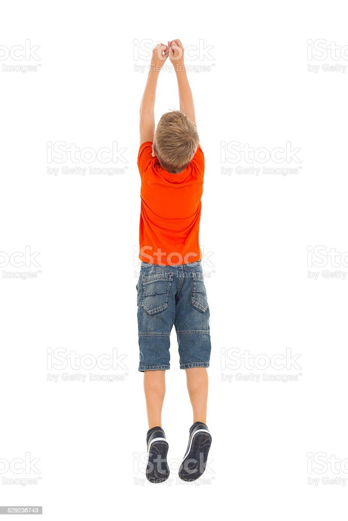 rear view of young boy jumping stock photo
