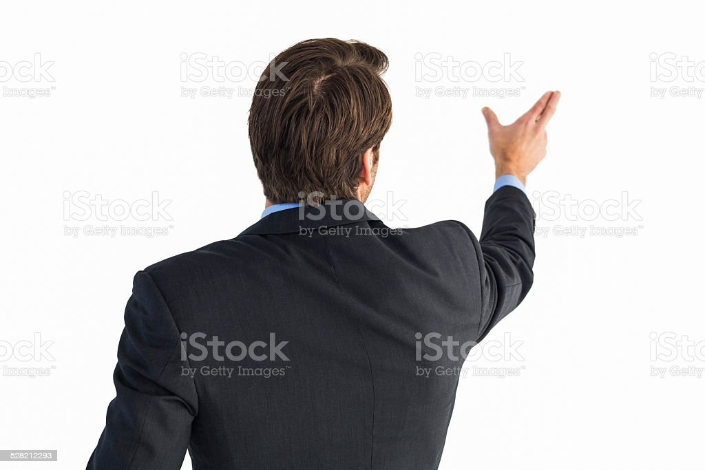 Rear view of young businessman in suit pointing stock photo