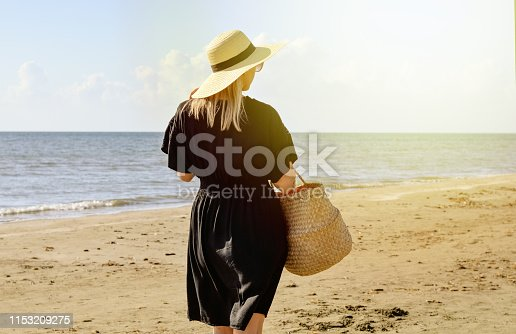 Rear view of young  caucasian woman with dress  ,  straw hat and basket waliking  on beach   and relaxing . Summer holidays . Bright warm filter .