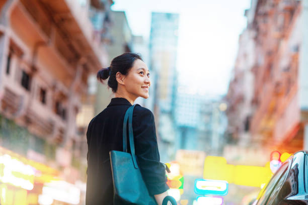 Rear view of young Chinese businesswoman standing by car looking away in Hong Kong stock photo