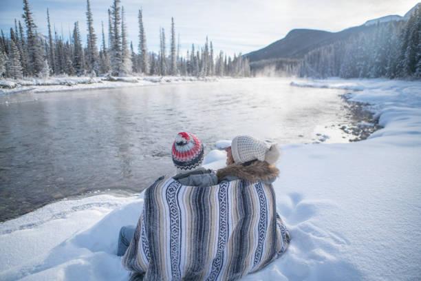 Blick auf das junge Ehepaar, das die Natur im Winter in den schneebedeckten Bergen bei Sonnenuntergang betrachtet – Foto