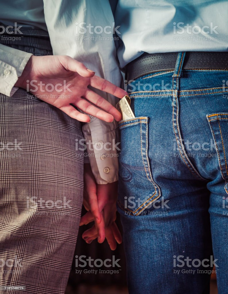 Rear View Of young couple holding hands, second hand wife pulls money...