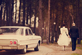 Rear view of young couple in wedding dress and wedding suit walking in forest. Chevrolet impala car follow them from behind