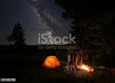 Rear view of young couple tourists enjoying the starry sky with a bright Milky way under the mighty trees near the campfire and orange illuminated tent in mountains. Romantic night camping near forest