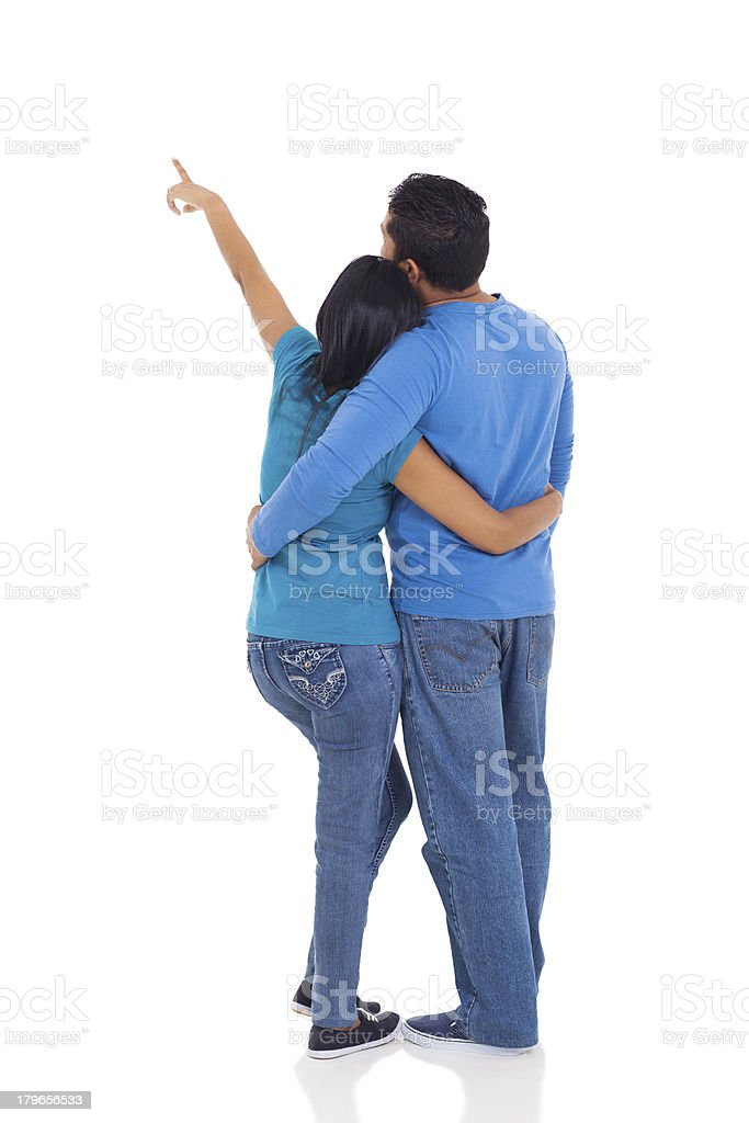 rear view of young couple pointing at copy space royalty-free stock photo