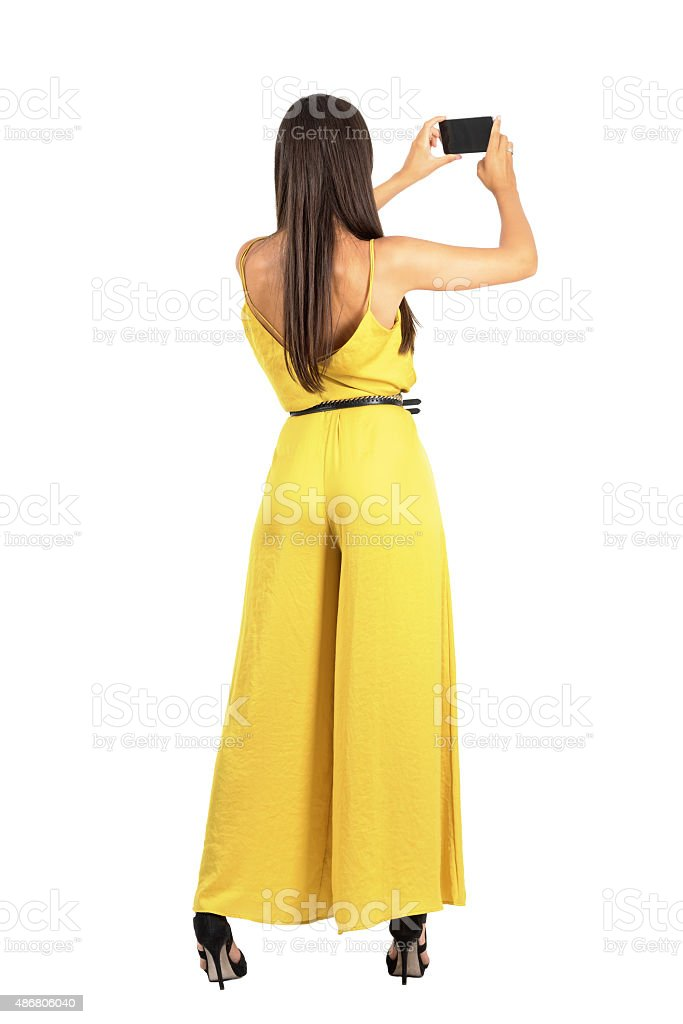 Rear view of young elegant woman taking photo with smartphone stock photo