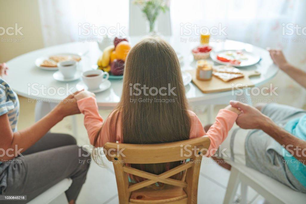 Family praying before eating
