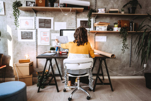 Rear view of young female entrepreneur in the office stock photo