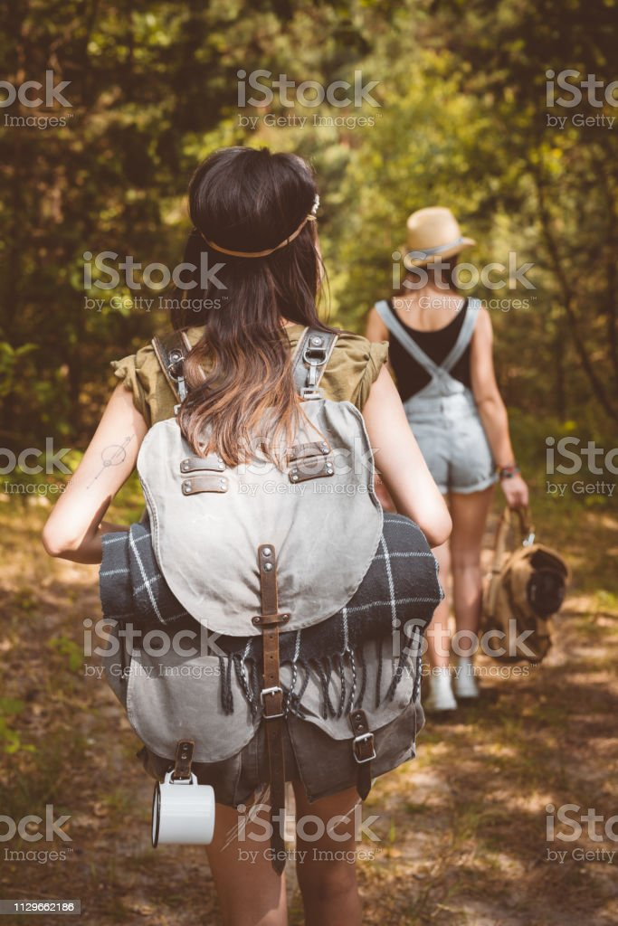 Rear view of young females hiking in forest Rear view of females hiking in forest. Friends are walking with backpacks. They are spending weekend together. 20-24 Years Stock Photo