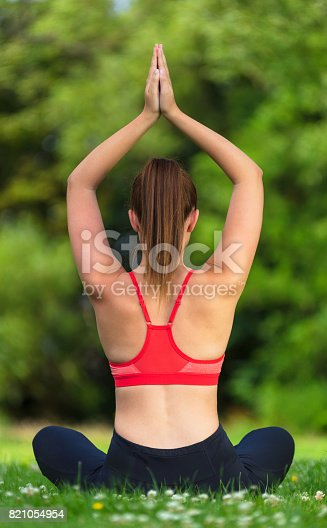 Rear view of young fit healthy woman female or girl practicing yoga seated mountain pose on a mat outside in a natural tranquil green environment