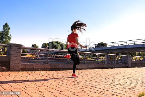 istock Rear view of young fitness woman wearing sports clothing exercising outdoors. 1170147030