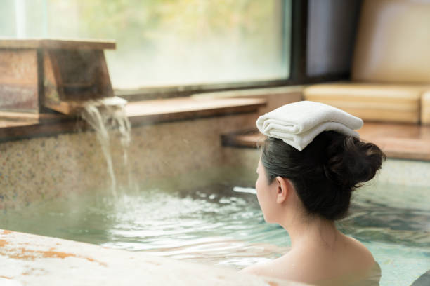 rear view of young girl enjoy the hot springs rear view of young girl enjoy the hot springs and put a towel on her head while water flows on the background. hot spring stock pictures, royalty-free photos & images