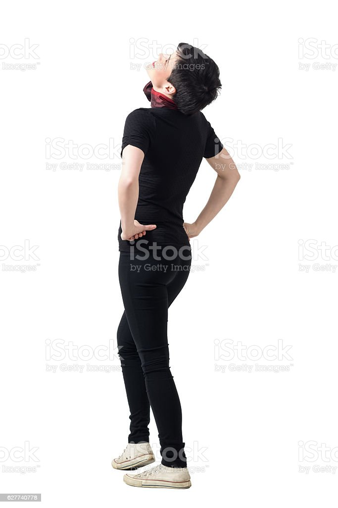 Rear view of young happy woman laughing and looking up stock photo