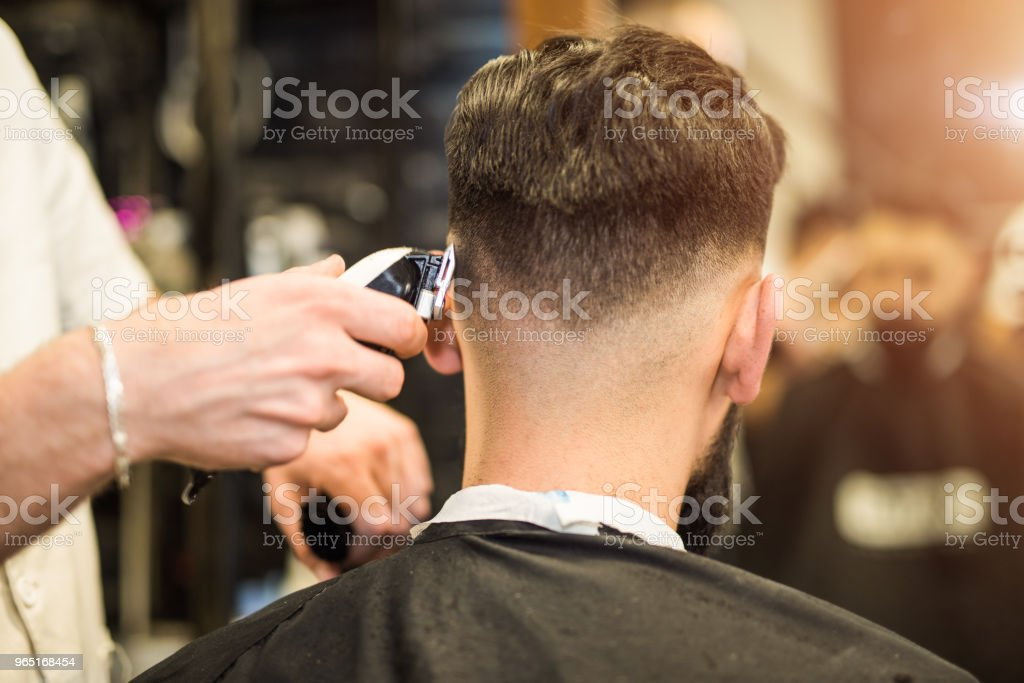 Rear view of young man getting a haircut. royalty-free stock photo