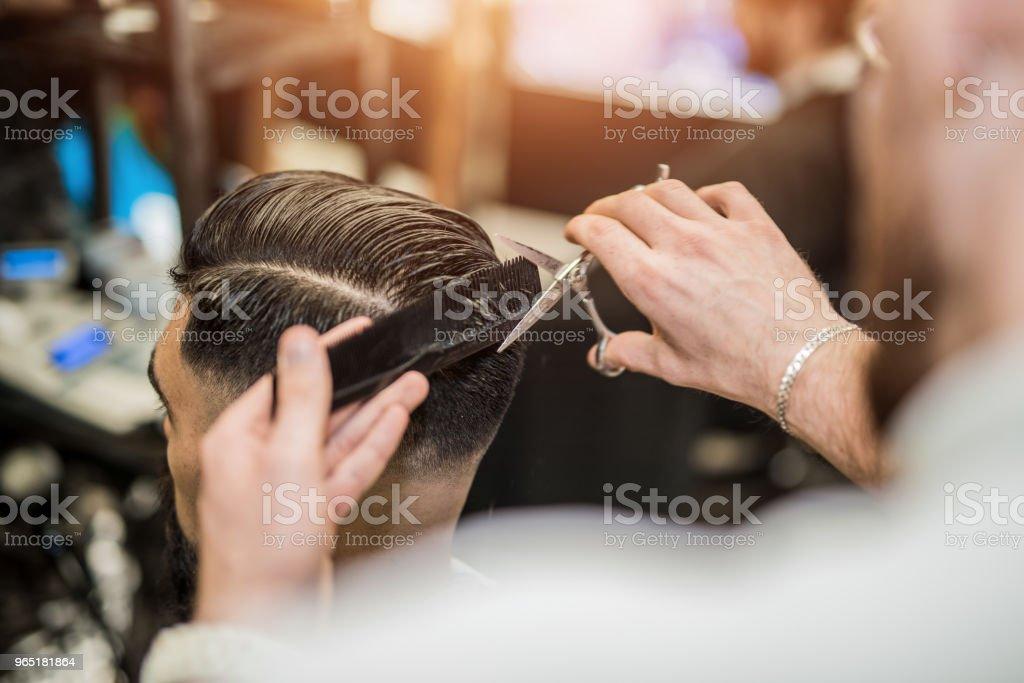 Vue arrière du jeune homme, obtenant une coupe de cheveux moderne. - Photo de A la mode libre de droits