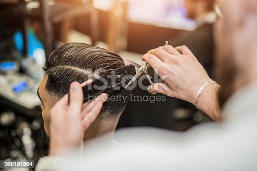 istock Rear view of young man getting a modern haircut. 965181864