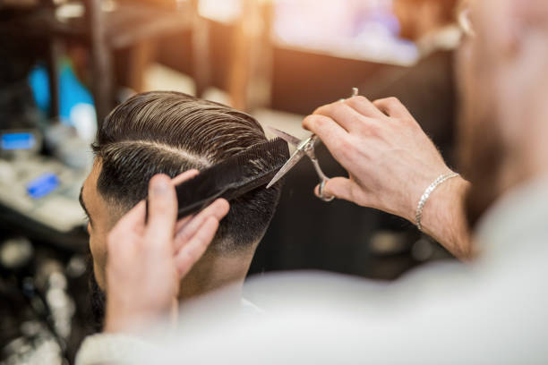 Rear view of young man getting a modern haircut. stock photo