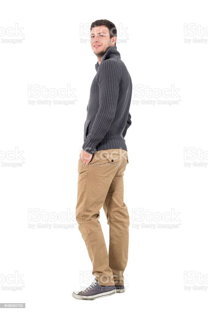 Rear view of young man in jumper smiling at camera stock photo