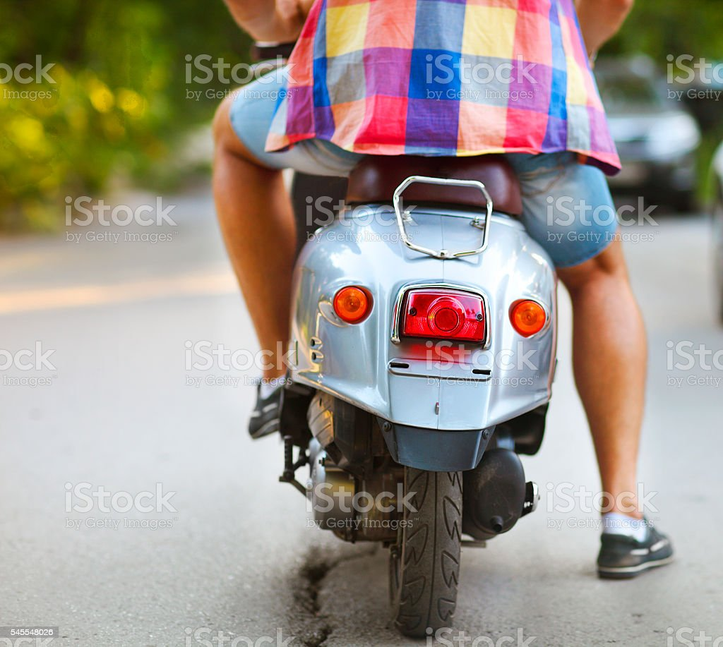 Rear view of young man riding scooter along the street stock photo